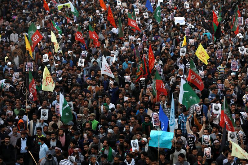 Pakistani Shi'ite Muslims carry flags and signs to protest the death of Iranian military commander Qassem Soleimani, who was killed in a airstrike near Baghdad, as they march on a road leading towards the U.S. consulate in Karachi