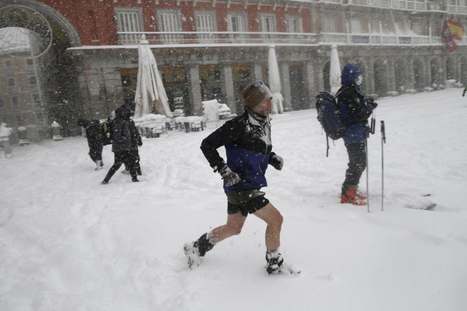 A man runs crossing the Plaza Mayor during a heavy snowfall in Madrid, Spain, Saturday, Jan. 9, 2021. An unusual and persistent blizzard has blanketed large parts of Spain with snow, freezing traffic and leaving thousands trapped in cars or in train stations and airports that had suspended all services as the snow kept falling on Saturday. The capital, Madrid, and other parts of central Spain activated for the first time its red weather alert, its highest, and called in the military to rescue people from cars vehicles trapped in everything from small roads to the city's major thoroughfares. (AP Photo/Andrea Comas)
