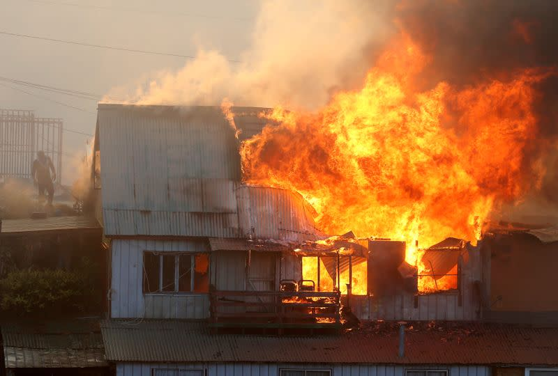 A house burns following the spread of wildfires in Valparaiso