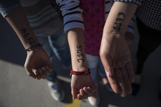 Lorena and her two children hold out their arms to show the numbers they were given to be on a list at Casa del Migrante to seek political asylum in the United States on Nov. 28, 2018. (Photo: Adria Malcolm for Yahoo News)