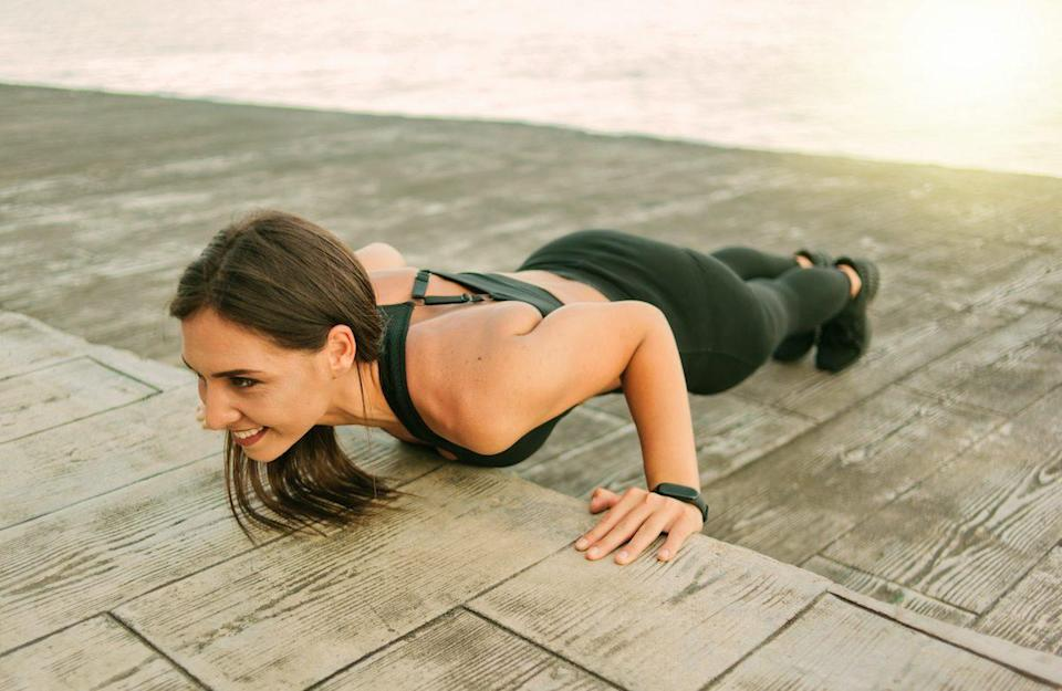Young fit woman in sportswear doing push ups exercise on the beach