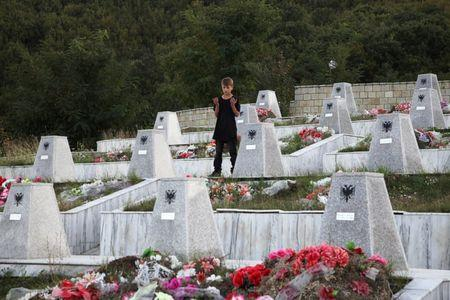 A boy prays at the grave of a relative, who was one of the forty-five ethnic Albanians killed by Serbian forces in January 1999, in the Recak village, Kosovo September 22, 2016. REUTERS/Hazir Reka