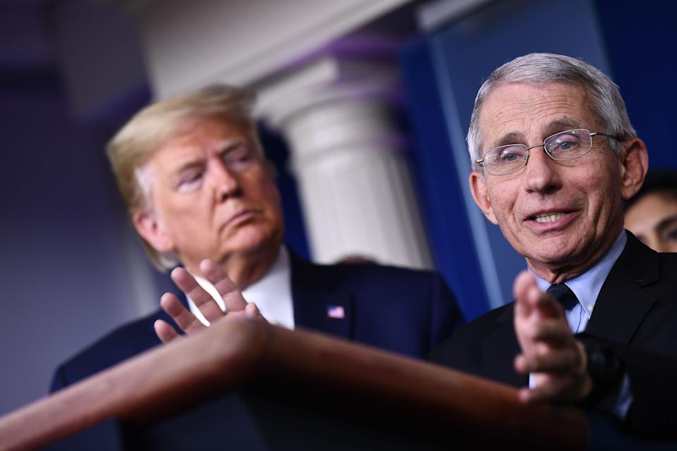 Dr. Anthony Fauci speaks as US President Donald Trump listens during the daily press briefing on the Coronavirus pandemic situation at the White House on March 17, 2020 in Washington, DC. - The coronavirus outbreak has transformed the US virtually overnight from a place of boundless consumerism to one suddenly constrained by nesting and social distancing.The crisis tests all retailers, leading to temporary store closures at companies like Apple and Nike, manic buying of food staples at supermarkets and big-box stores like Walmart even as many stores remain open for business -- albeit in a weirdly anemic consumer environment. (Photo by Brendan Smialowski / AFP) (Photo by BRENDAN SMIALOWSKI/AFP via Getty Images)