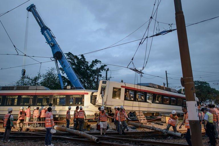 Workers inspect and remove a derailed train carriage in Hong Kong, on May 17, 2013
