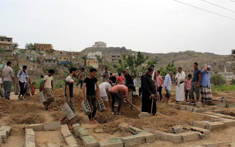 People gather at mass graves in Taiz, where victims of Covid-19 are laid to rest - Reuters