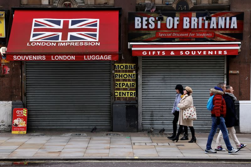 People walk in pairs past closed shops