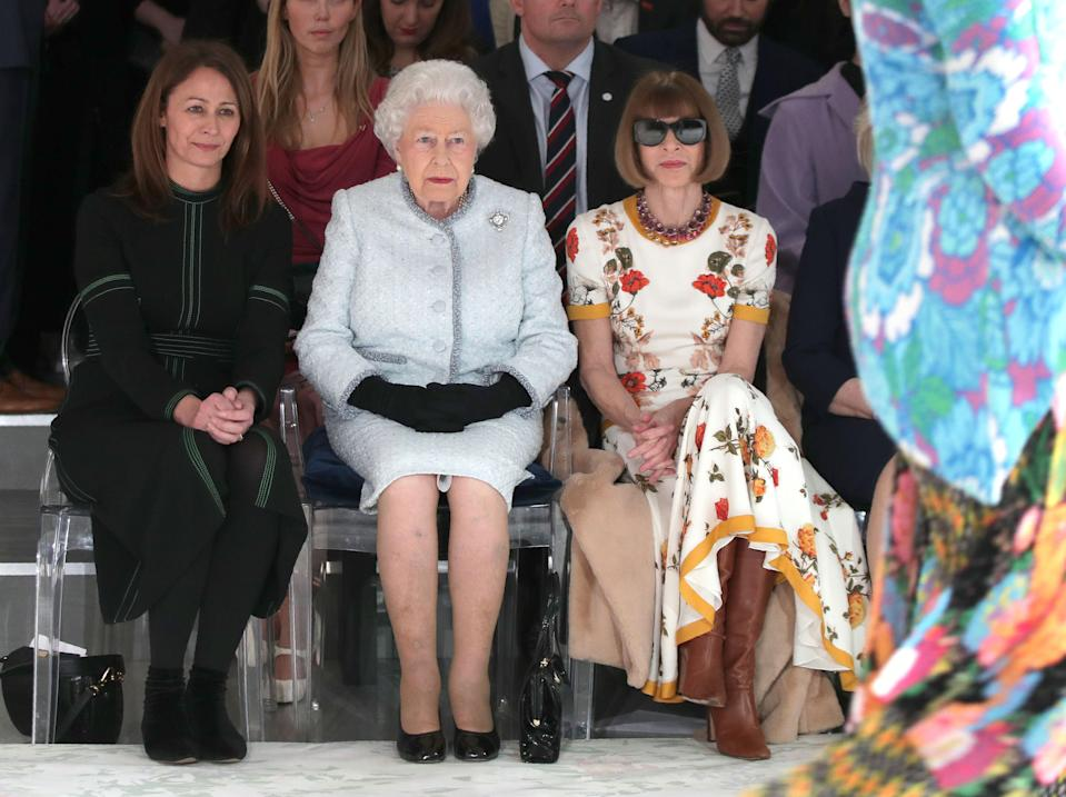 Britain's Queen Elizabeth II, accompanied by Chief Executive of the British Fashion Council (BFC), Caroline Rush (L) and  British-American journalist and editor, Anna Wintour (R), views British designer Richard Quinn's runway show before presenting him with the inaugural Queen Elizabeth II Award for British Design, during her visit to London Fashion Week's BFC Show Space in central London on February 20, 2018. / AFP PHOTO / POOL / Yui Mok        (Photo credit should read YUI MOK/AFP via Getty Images)