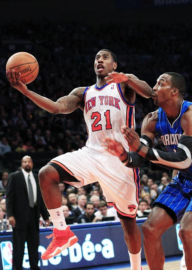New York Knicks' Iman Shumpert (21) drives past Orlando Magic's Dwight Howard (12) during the first half of an NBA basketball game, Wednesday, March 28, 2012, in New York. (AP Photo/Frank Franklin II)