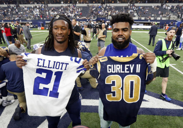 The Rams' Todd Gurley, holding up Ezekiel Elliott's jersey after a 2017 game against the Cowboys, is the highest-paid running back in the NFL. (AP)