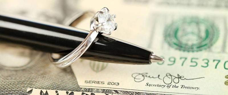 Wedding ring on pen, on banknotes background