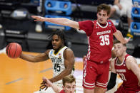 Baylor guard Davion Mitchell (45) makes a pass under Wisconsin forward Nate Reuvers (35) in the second half of a second-round game in the NCAA men's college basketball tournament at Hinkle Fieldhouse in Indianapolis, Sunday, March 21, 2021. (AP Photo/Michael Conroy)