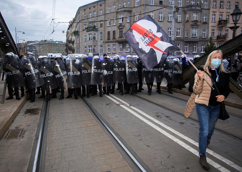"""A woman carries a placard reading """"Women's Strike"""" as police block a road during a protest against imposing further restrictions on abortion law, in Wroclaw, Poland October 23, 2020. Krzysztof Cwik/Agencja Gazeta/via REUTERS ATTENTION EDITORS - THIS IMAGE WAS PROVIDED BY A THIRD PARTY. POLAND OUT. NO COMMERCIAL OR EDITORIAL SALES IN POLAND. TPX IMAGES OF THE DAY"""