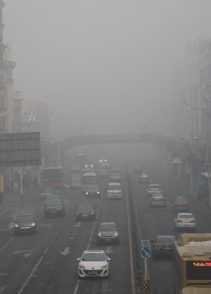 HARBIN, CHINA - DECEMBER 03: (CHINA OUT) Vehicles are driven along a road as heavy smog engulfs the city on December 3, 2013 in Harbin, China. Harbin Meteorological Bureau issued an orange warning on smog on Tuesday morning. (Photo by ChinaFotoPress/ChinaFotoPress via Getty Images)