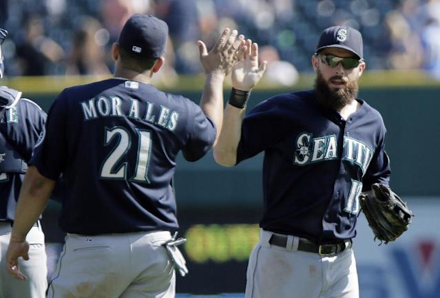 Seattle Mariners' Dustin Ackley (13) celebrates an 8-1 win over the Detroit Tigers with teammate Kendrys Morales (21) after a baseball game Sunday, Aug. 17, 2014, in Detroit. (AP Photo/Duane Burleson)