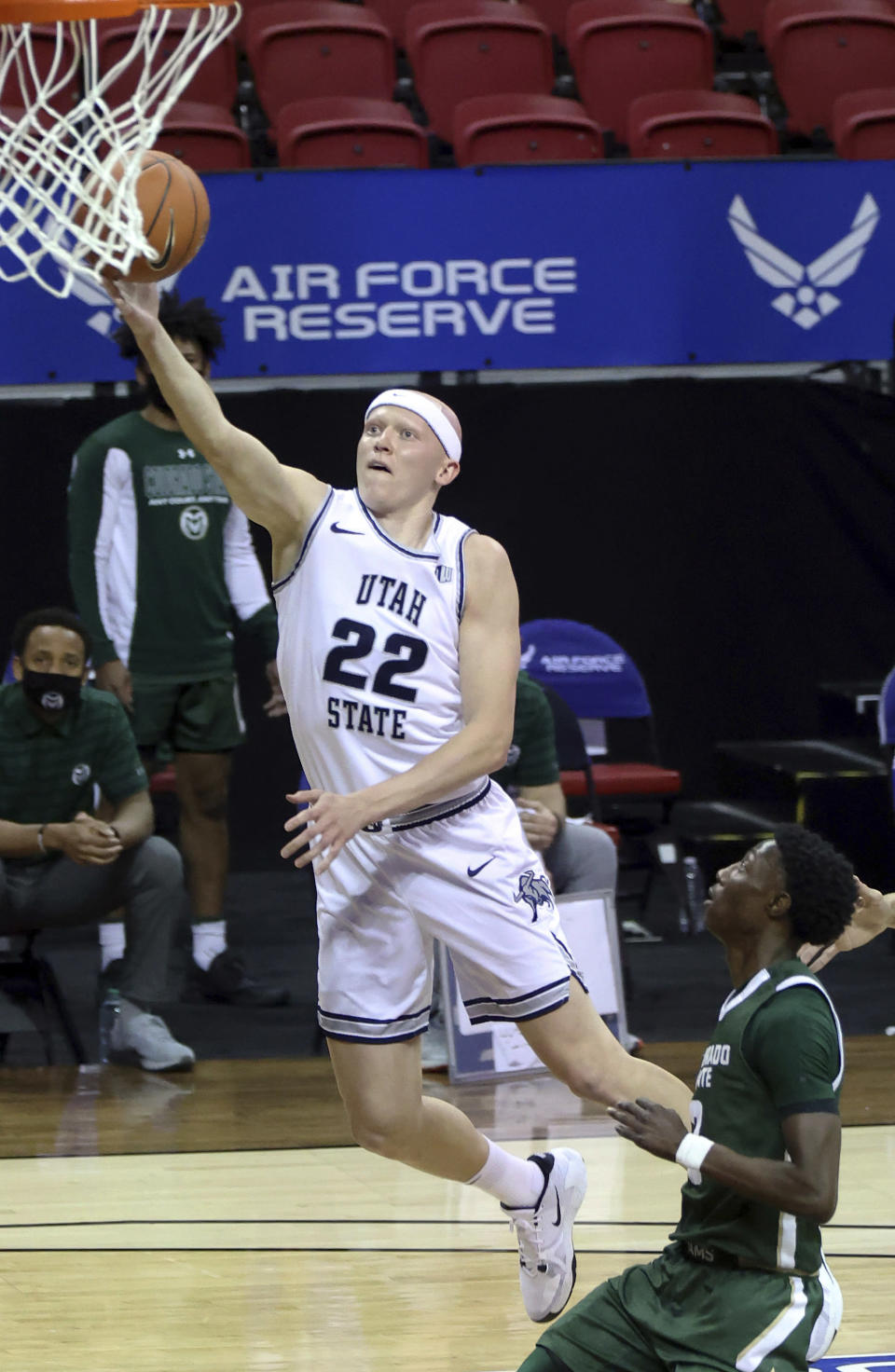 Utah State guard Brock Miller (22) shoots as Colorado State guard Kendle Moore (3) defends during the first half of an NCAA college basketball game in the semifinals of the Mountain West Conference men's tournament Friday, March 12, 2021, in Las Vegas. (AP Photo/Isaac Brekken)
