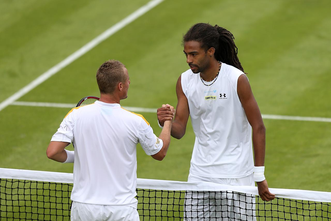 Germany's Dustin Brown (right) shakes hands with Australia's Lleyton Hewitt after their match during day three of the Wimbledon Championships at The All England Lawn Tennis and Croquet Club, Wimbledon.