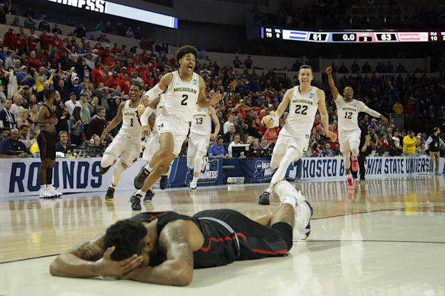 Michigan players celebrate Jordan Poole's buzzer-beater as Houston's Devin Davis lies face-down on the court. (Getty)