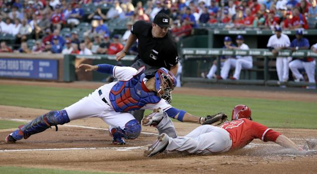 Home plate umpire Lance Barrett watches as Texas Rangers catcher Robinson Chirinos is unable to tag out Los Angeles Angels' Mike Trout who scored on a Josh Hamilton double in the first inning of a baseball game, Thursday, July 10, 2014, in Arlington, Texas. (AP Photo/Tony Gutierrez)