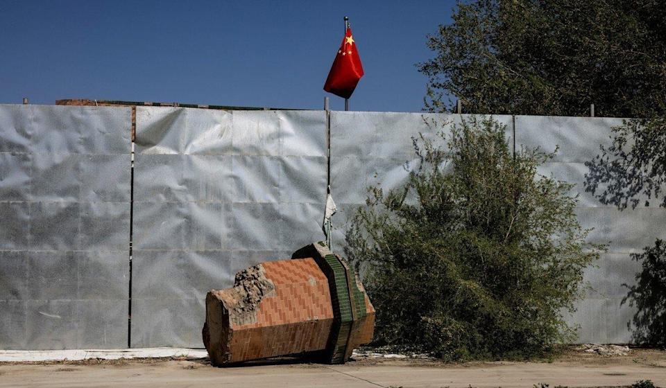 A broken-off minaret from the Xinqu Mosque lies near a Chinese national flag outside Urumqi, in the Xinjiang Uygur autonomous region, on May 6. Photo: Reuters