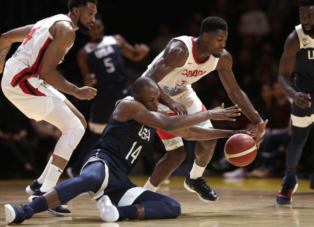 Canada's Melvin Ejim, second right, and United States Khris Middleton, second left, compete for the ball during their exhibition basketball game in Sydney, Australia, Monday, Aug. 26, 2019. (AP Photo/Rick Rycroft)