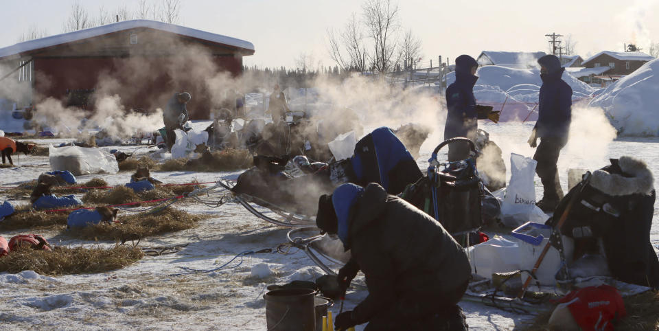 Mushers handle their dog care on a cold morning in the McGrath, Alaska, checkpoint during the Iditarod Trail Sled Dog Race on Saturday, March 13, 2021. (Zachariah Hughes/Anchorage Daily News via AP, Pool)