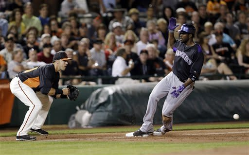 Colorado Rockies' Dexter Fowler, right, arrives safely at third base with a triple next to San Francisco Giants third baseman Adam Duvall during the third inning of a spring training baseball game Thursday, March 21, 2013, in Scottsdale, Ariz. (AP Photo/Marcio Jose Sanchez)