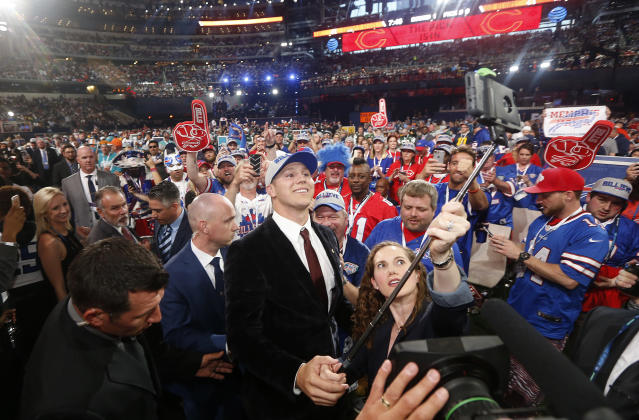 FILE - In this April 26, 2018, file photo,Wyoming's Josh Allen, center, takes a selfie of himself with Buffalo Bills fans after being selected by the team during the first round of the NFL football draft, in Arlington, Texas. It has never been easy being a sports fan in Buffalo, where losing has been customary. A renewed sense of hope has suddenly arisen in this rust-belt city after the Bills selected quarterback Josh Allen in the first round of the draft and the Sabres won the NHL draft lottery.(AP Photo/Michael Ainsworth, File)