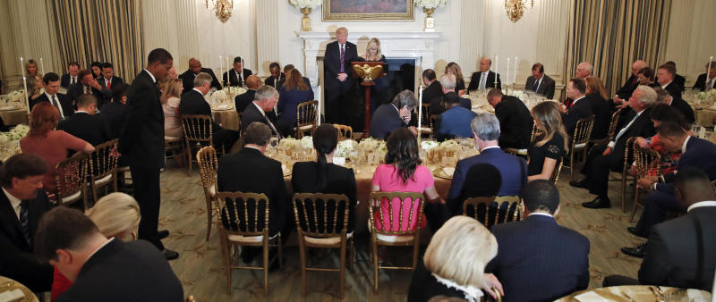 President Donald Trump bows his head as his spiritual adviser Paula White prays during an Aug. 27, 2018, dinner for evangelical leaders at the White House.