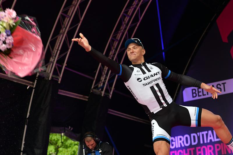 Germany's Marcel Kittel throws a bunch of flowers as he celebrates on the podium after winning the 218-kilometer (135-mile) second stage of the Giro d'Italia, Tour of Italy cycling race, from Belfast to Belfast, Northern Ireland, Saturday May 10, 2014. (AP Photo/Giuan Mattia D'Alberto)