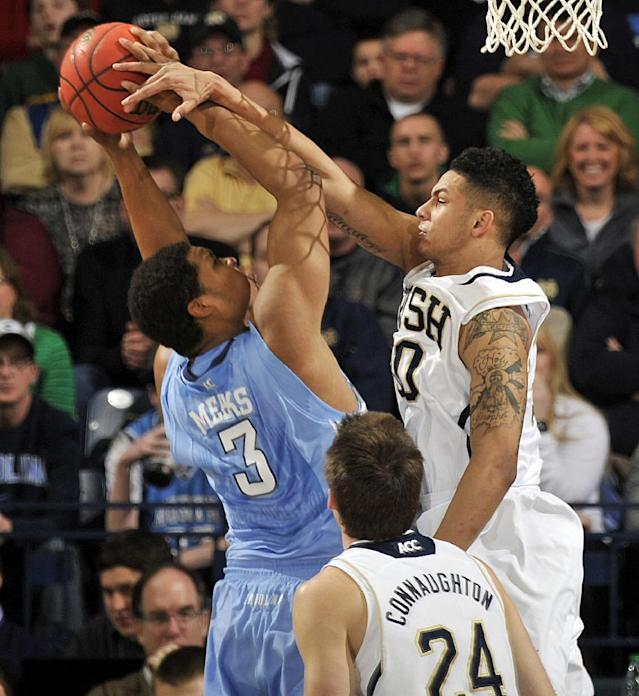 North Carolina forward Kennedy Meeks, left, puts up a shot as he is fouled by Notre Dame forward Zach Auguste during the first half of an NCAA college basketball game Saturday, Feb. 8, 2014, in South Bend, Ind. (AP Photo/Joe Raymond)