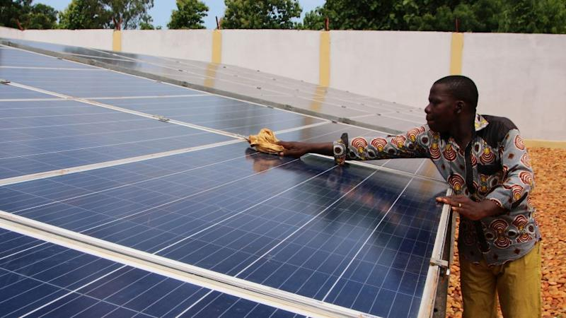 A technician cleans solar panels, part of the BBOXX and EDF solar energy system used to provide electricity to Sikpe Afidegnon village