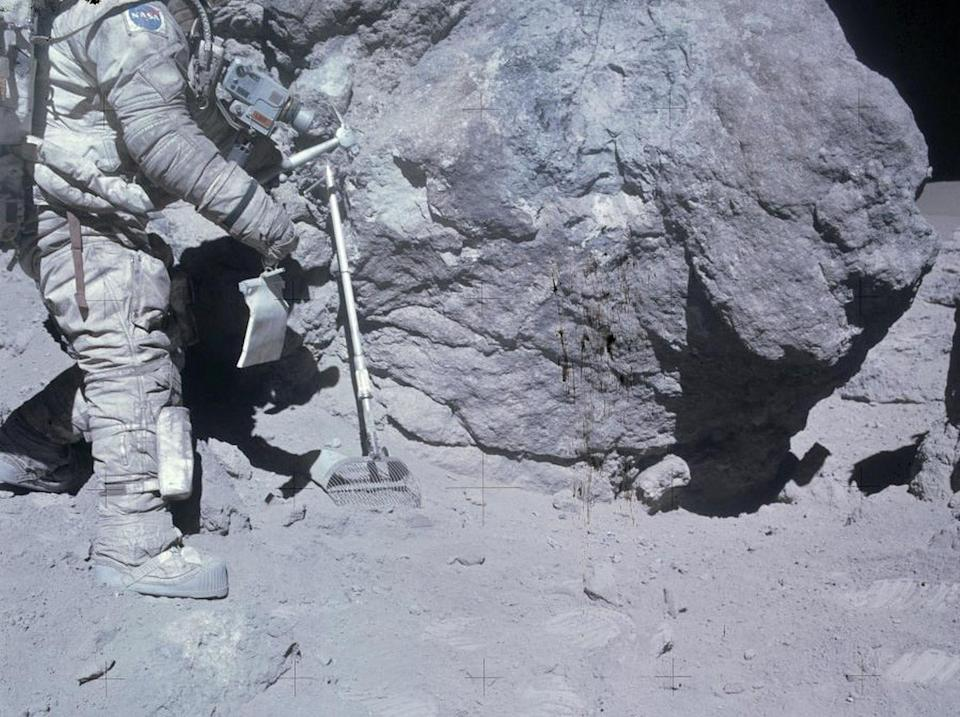Apollo 16 astronaut Charlie Duke collects lunar samples during a moonwalk. <cite>NASA/Johnson Space Center</cite>