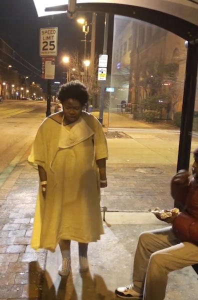 This Tuesday, Jan. 9, 2018, still image taken from video provided by Imamu Baraka shows a woman discharged from a Baltimore hospital wearing only a gown and socks on a cold winter's night. Baraka, identified in local reports as the person who sought to help the woman, told The Associated Press he was so angry he decided to record Tuesday night's events on cellphone video, fearing no one would believe him if he reported a woman being left at a bus stop like that. (Imamu Baraka via AP)