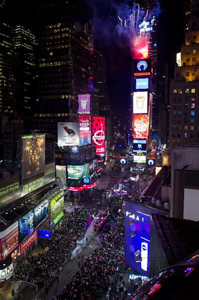 Looking from the Marriott Marquis hotel, fireworks erupt from One Times Square as the Waterford Crystal ball that will mark the new year is raised into position at six hours before midnight for New Year's Eve celebrations in New York Tuesday, Dec. 31, 2013. (AP Photo/Craig Ruttle)