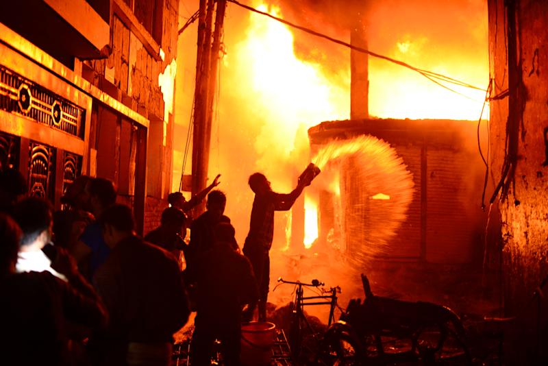 Firefighters and local people help douse a fire in Dhaka, Bangladesh on Feb. 20, 2019. A devastating fire raced through at least five buildings in an old part of Bangladesh's capital and killed scores of people. (Photo: Mahmud Hossain Opu/AP)