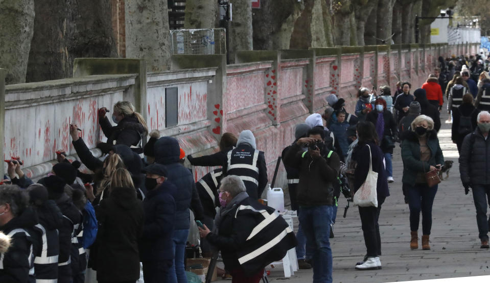 People paint red hearts onto the COVID-19 Memorial Wall mourning those who have died, along the embankment opposite the Houses of Parliament on the Embankment in London, Monday, April 5, 2021. Hearts are being painted onto the wall in memory of the many thousands of people who have died in the UK from coronavirus. (AP Photo/Frank Augstein)