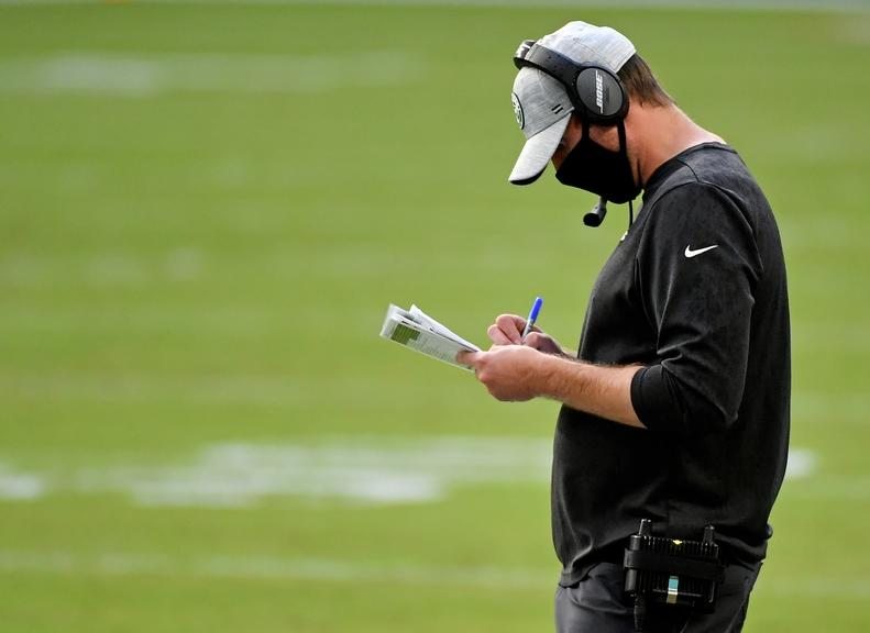 Adam Gase looks at call sheet during Jets game against Dolphins