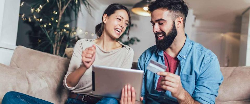 Smiling couple using digital tablet and credit card at home