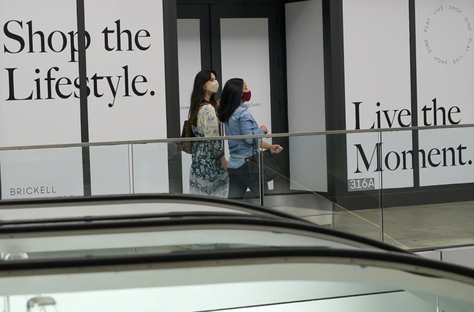 Shoppers walk past a vacant storefront at Brickell City Centre, Friday, Nov. 6, 2020, in Miami. The spread of COVID-19 vaccines will power a stronger global economic recovery in 2021, the International Monetary Fund forecast Tuesday, Jan. 26, 2021. (AP Photo/Lynne Sladky)