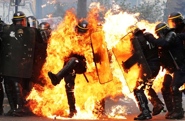 <p>MAY 1, 2017 – French CRS anti-riot police officers are engulfed in flames as they face protesters during a march for the annual May Day workers' rally in Paris. (Photo: Zakaria Abdelkafi/AFP/Getty Images) </p>
