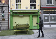 A man walks past a closed bar in Dublin, Ireland, Wednesday, Oct. 21, 2020. With COVID-19 cases on the rise, the government has imposed a tough new lockdown, shutting down non-essential shops, limiting restaurants to takeout service and ordering people to stay within five kilometers (three miles) of their homes for the next six weeks. (AP Photo/Peter Morrison)