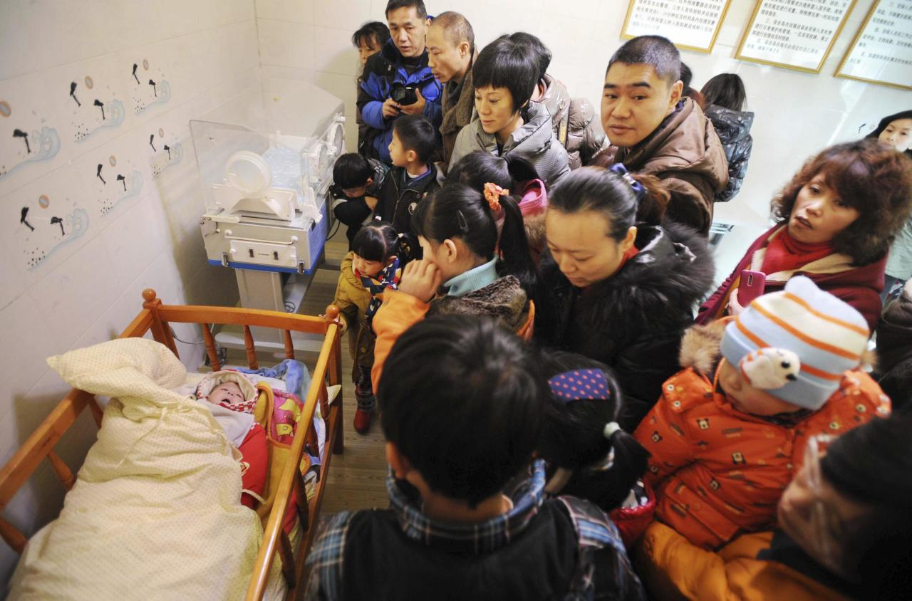 "Residents visit an abandoned baby (L) lying in a crib at a baby hatch in Guiyang, Guizhou province January 12, 2014. Dozens of babies have been secretly dropped off at ""baby safety islands"", or ""baby hatches"", set up since late last year under a scheme aimed at protecting unwanted offspring. Chinese media frequently report harrowing tales of babies being abandoned, a problem attributed to young mothers unaware they are pregnant, the birth of an unwanted girl in a society which puts greater value on boys or China's strict family planning rules. Chinese orphanages have seen a falling number of abandoned children since 2005, but officials estimate some 10,000 unwanted children are still received each year. An unknown number of abandoned babies are also adopted informally. Picture taken January 12, 2014. REUTERS/Stringer (CHINA - Tags: HEALTH SOCIETY) CHINA OUT. NO COMMERCIAL OR EDITORIAL SALES IN CHINA"
