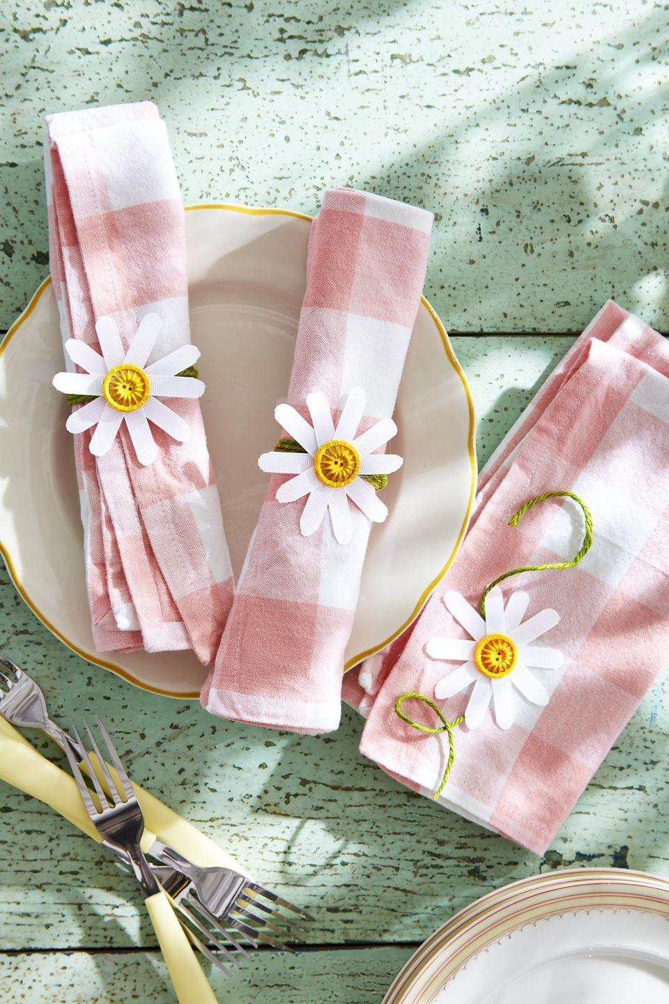 "<p>Created from grosgrain ribbon and vintage or new buttons, these sweet DIY napkin rings will brighten up any table</p><p><strong>To make:</strong> For each napkin ring, cut 3/8-inch-wide white grosgrain ribbon into five 3-inch-long pieces; round ends. Glue one piece on top of the next, offsetting as you go to create a flower shape. Glue a yellow button in center and a length of green twine to back for tying.</p><p><a class=""link rapid-noclick-resp"" href=""https://www.amazon.com/VATIN-Solid-Grosgrain-Ribbon-50-Yard/dp/B072F2MXW2/ref=sr_1_3?tag=syn-yahoo-20&ascsubtag=%5Bartid%7C10050.g.1652%5Bsrc%7Cyahoo-us"" rel=""nofollow noopener"" target=""_blank"" data-ylk=""slk:SHOP RIBBON"">SHOP RIBBON</a></p>"