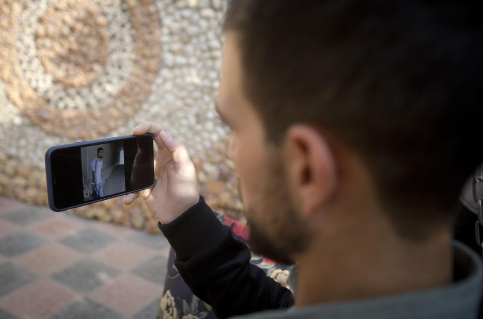 Palestinian Karam Qawasmi looks at a video, which appears to have been taken by a member of the security forces, showing when he was shot in the back by Israeli forces in an incident last year, in the garden of his house, in the West Bank city of Hebron, Sunday, Nov. 10, 2019. Qawasmi said that the footage shows just a small part of what was a horrifying day for him. In his first interview since the video emerged last week, Qawasmi said he was run over by a military jeep, then beaten for several hours before troops released him, only to shoot him in the back with a painful sponge-tipped bullet as he walked away. (AP Photo/Majdi Mohammed)