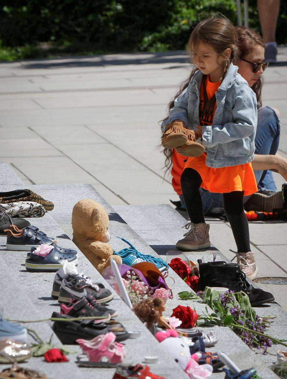 <p>A girl tries to put a pair of shoes on the staircase while attending a memorial event for the 215 children whose remains have been found buried at a former Kamloops residential school outside Vancouver Art Gallery in Vancouver, British Columbia, Canada, May 29, 2021 .The reported discovery of the remains of 215 indigenous children at a former residential school in Kamloops in western Canada has shocked Canadian people.In a press release on Friday, the British Columbia Assembly of First Nations said it is grieving the location of the 215 children. (Photo by Liang Sen/Xinhua via Getty Images)</p>