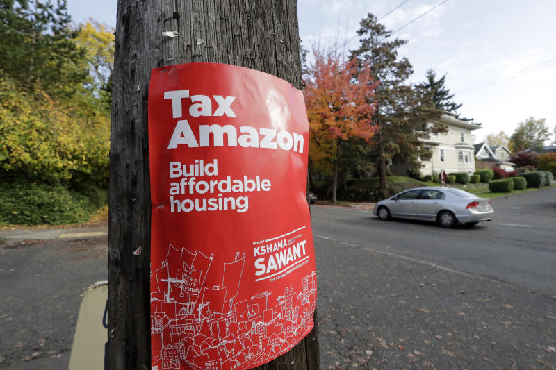 File-In this Wednesday, Oct. 23, 2019 file photo, a campaign poster for Seattle City Council incumbent candidate Kshama Sawant is posted outside her campaign headquarters in Seattle. In Seattle's City Council races retail giant Amazon made unprecedented donations totaling about $1.5 million to a political action committee that supported a slate of candidates perceived to be friendlier to business, but early returns suggest the company could end up with fewer allies on the Council. (AP Photo/Elaine Thompson)