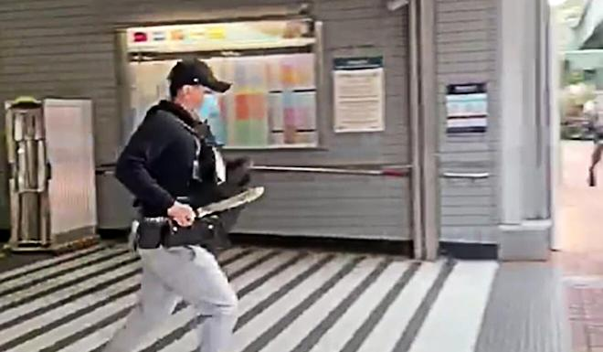 One of the alleged assailants runs from the Tai Wai MTR station clutching a 30cm knife. Photo: Facebook