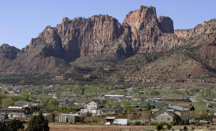 FILE - Hildale, Utah sits at the base of red rock cliff mountains with its sister city, Colorado City, Ariz. in the foreground in this Thursday, April 20, 2006 file photo. An attorney for local law enforcement in the two polygamous towns, where most residents are members of the Fundamentalist Church of Jesus Christ of Latter Day Saints run by the group's jailed leader Warren Jeffs, says the U.S. Justice Department plans to sue both communities, claiming religious discrimination. (AP Photo/Douglas C. Pizac)