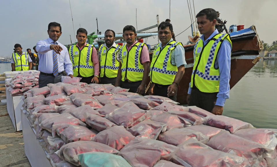 Sri Lankan police officers belonging to the narcotics unit, in green jackets, stand next to a seized haul of narcotics at a fishery harbor in Colombo, Sri Lanka, on May 3, 2020. For years, authorities in Sri Lanka have tried to rid the Indian Ocean island nation of illegal drugs. But a drug ring allegedly including more than a dozen officers from a key national narcotics unit has exposed how much of a challenge that goal brings. (AP Photo)