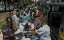 Homeless people receive lunch in downtown in Sao Paulo, Brazil, on March 23, 2021